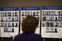 """An advocate and survivor of sexual abuse, looks at the photos of Catholic priests accused of sexual misconduct by victims during a news conference Thursday, Dec. 6, 2018, in Orange, Calif. Advocates for survivors of child sex abuse say they have compiled a list of 72 priests who served in the Southern California Diocese of Orange and who are accused of abusing kids. Lawyer Mike Reck on Thursday said that's many more than those reported by the Diocese and demanded greater transparency. The Diocese of Orange says the lawyers are trying to re-litigate old claims that the church takes any accusations of abuse """"extraordinarily seriously."""" (AP Photo/Jae C. Hong)"""