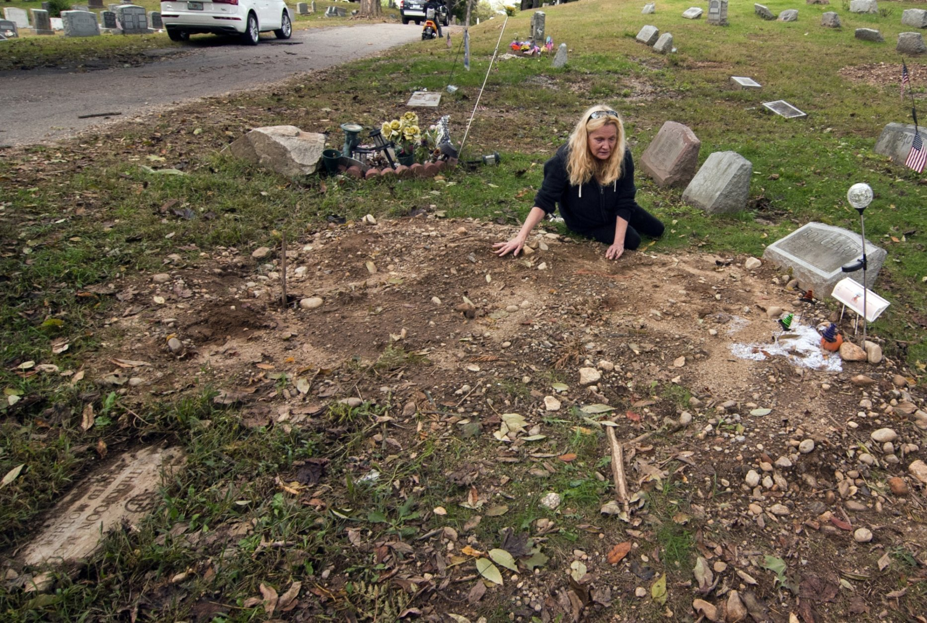 FILE - In this Oct. 3, 2018 file photo, a distraught Jean Stott, of Shelton, Conn., tries to find the exact spot where a family member is located after the tombstone, had been moved at Park Cemetery in Bridgeport, Conn. A mass desecration of graves at the cemetery has devastated dozens of families while police determine whether to file criminal charges. Authorities say gravestones and human remains at Park Cemetery in Bridgeport were moved to make way for the newly dead. (Christian Abraham/Hearst Connecticut Media via AP, File)