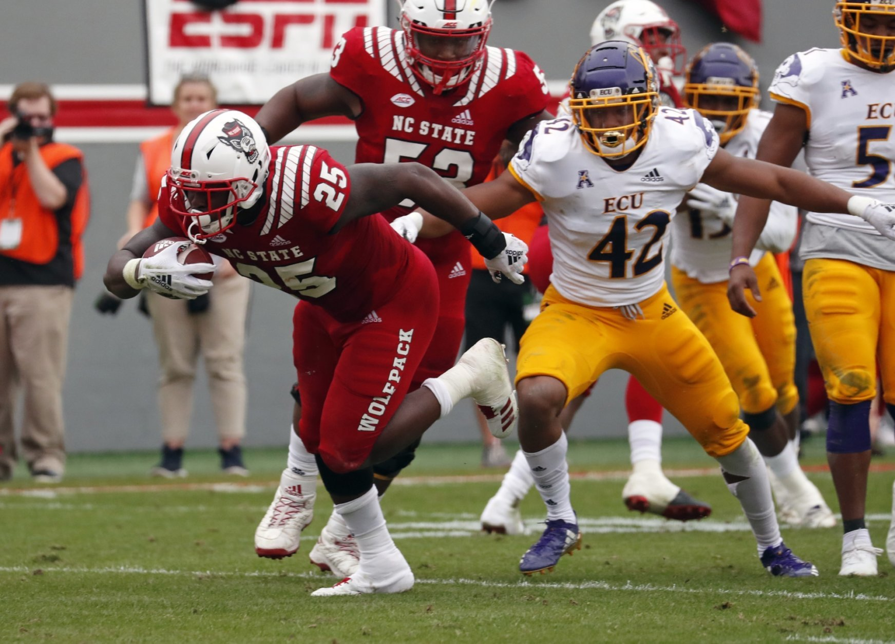 North Carolina State's Reggie Gallaspy II (25) breaks away from East Carolina's Devon Sutton (42) as he runs for a touchdown during the first half of NCAA college football game in Raleigh, N.C., Saturday, Dec. 1, 2018. (AP Photo/Chris Seward)