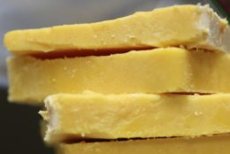 FILE - This May 28, 2015 file photo shows cheddar cheese Madison, Wis. The practice of adding color to cheddar cheese reaches back to when cheesemakers in England skimmed the butterfat from milk to make butter, according to Elizabeth Chubbuck of Murray's Cheese in New York. The leftover milk was whiter, so pigments were added to recreate butterfat's golden hue, she said. (Amber Arnold/Wisconsin State Journal via AP)