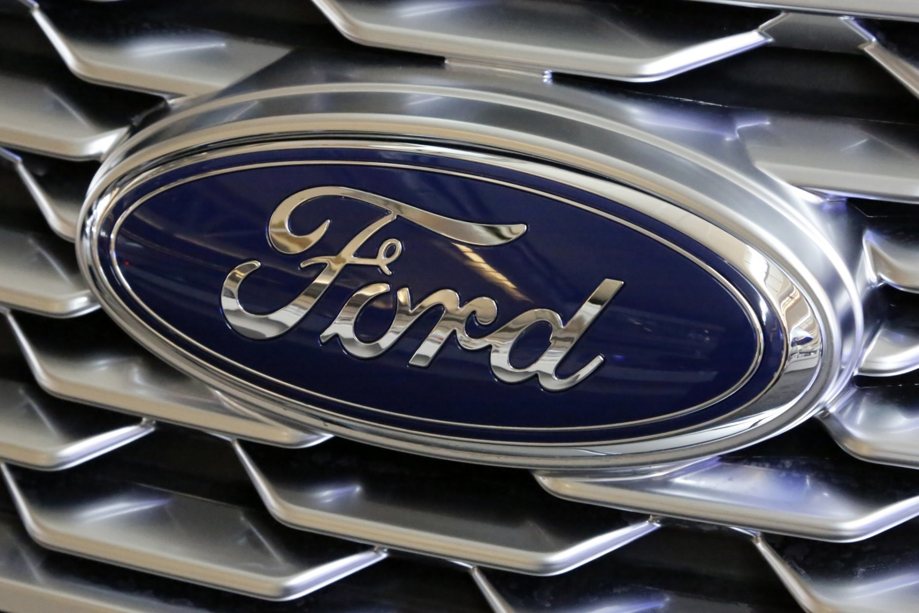 FILE - This Feb. 15, 2018 photo shows a Ford logo on display at the Pittsburgh Auto Show in Pittsburgh. (AP Photo/Gene J. Puskar)