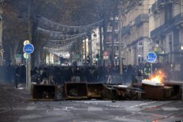 Demonstrators stand behind a burning bin during clashes, Saturday, Dec. 8, 2018 in Marseille, southern France. The rumble of armored police trucks and the hiss of tear gas filled central Paris on Saturday, as French riot police fought to contain thousands of yellow-vested protesters venting their anger against the government in a movement that has grown more violent by the week. (AP Photo/Claude Paris)