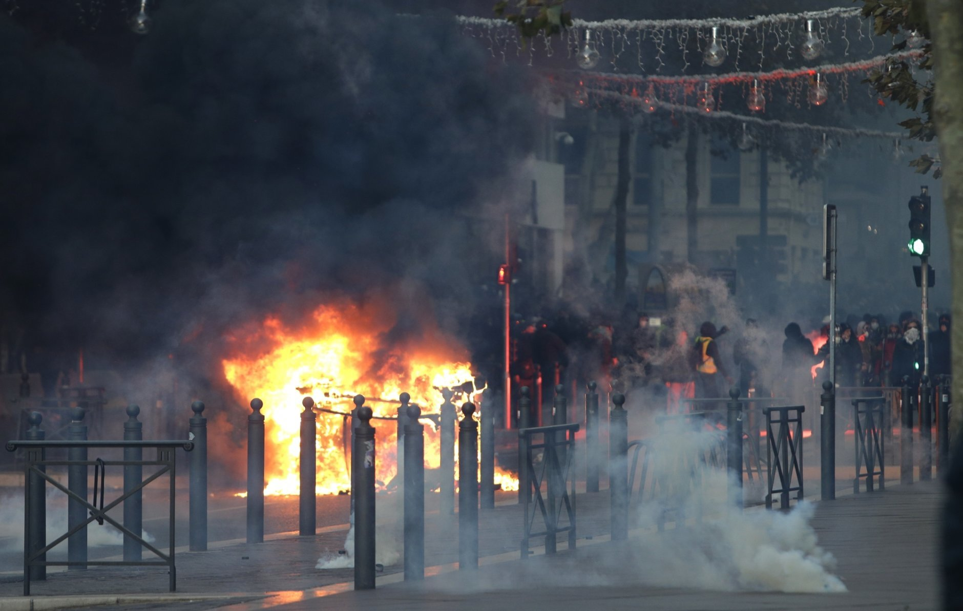 Demonstrators stand behind a burning car during clashes, Saturday, Dec. 8, 2018 in Marseille, southern France. French riot police fired tear gas and water cannon in Paris on Saturday, trying to stop thousands of yellow-vested protesters from converging on the presidential palace to express their anger at high taxes and French President Emmanuel Macron. (AP Photo/Claude Paris)