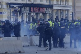 Riot police officers charge during clashes, Saturday, Dec. 8, 2018 in the Old Port of Marseille, southern France. The rumble of armored police trucks and the hiss of tear gas filled central Paris on Saturday, as French riot police fought to contain thousands of yellow-vested protesters venting their anger against the government in a movement that has grown more violent by the week. (AP Photo/Claude Paris)