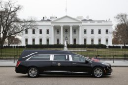 The hearse carrying the flag-draped casket of former President George H.W. Bush passes by the White House from the Capitol, heading to a State Funeral at the National Cathedral, Wednesday, Dec. 5, 2018, in Washington. AP Photo/Jacquelyn Martin).