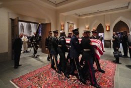 A military honor guard carries the flag-draped casket of former President George H.W. Bush after a funeral at St. Martin's Episcopal Church Thursday, Dec. 6, 2018, in Houston. (AP Photo/David J. Phillip, Pool)