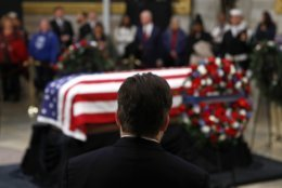A visitor pauses in front of the flag-draped casket of former President George H.W. Bush as he lies in state in the Capitol Rotunda in Washington, Tuesday, Dec. 4, 2018. (AP Photo/Patrick Semansky)