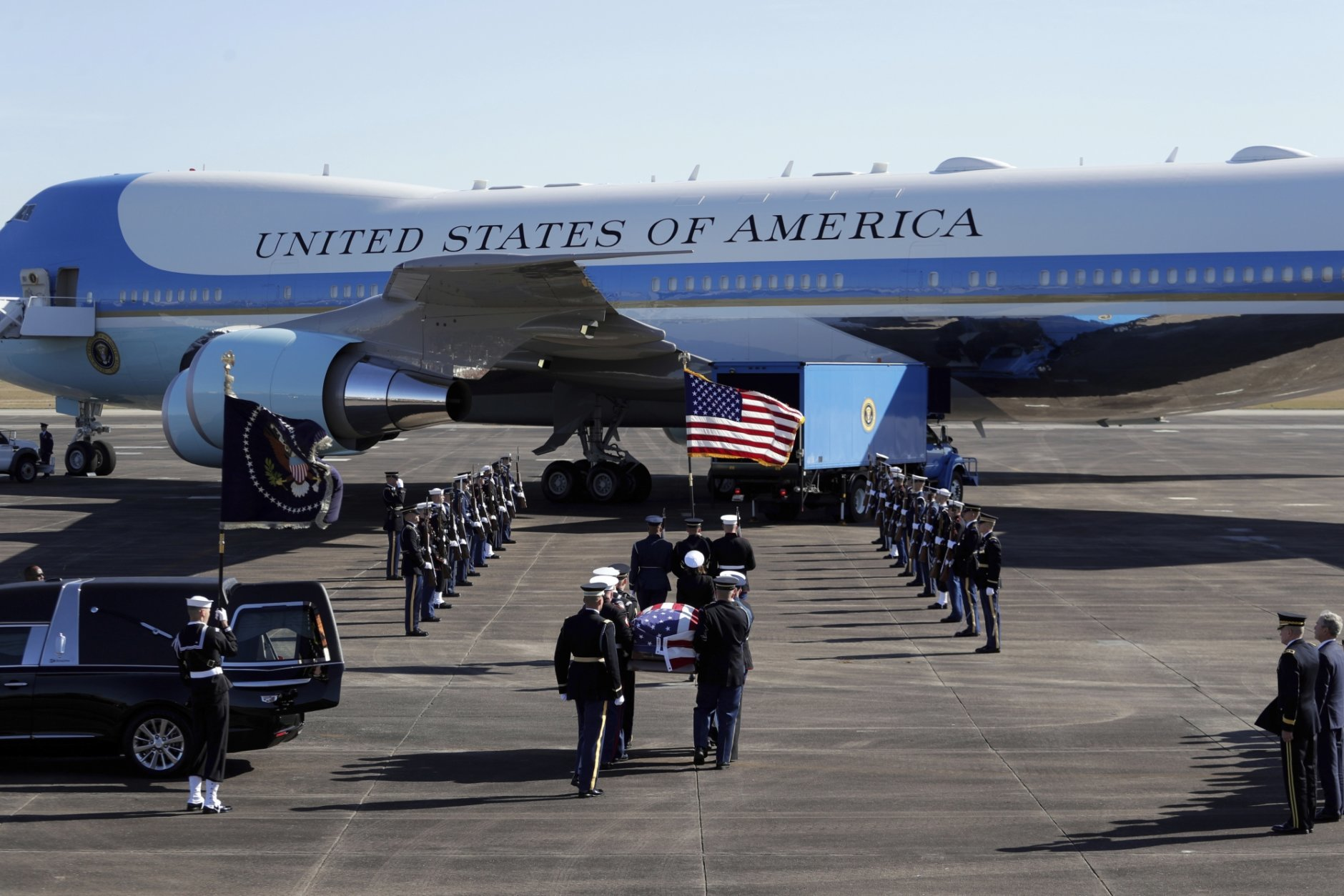 The flag-draped casket of former President George H.W. Bush is carried by a joint services military honor guard to Special Air Mission 41 at Ellington Field during a departure ceremony Monday, Dec. 3, 2018, in Houston. (AP Photo/Eric Gay)