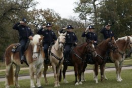 Police on horseback salute as the hearse carrying the flag-draped casket of former President George H.W. Bush heads to the Union Pacific train facility Thursday, Dec. 6, 2018, in Houston. (AP Photo/David J. Phillip, Pool)