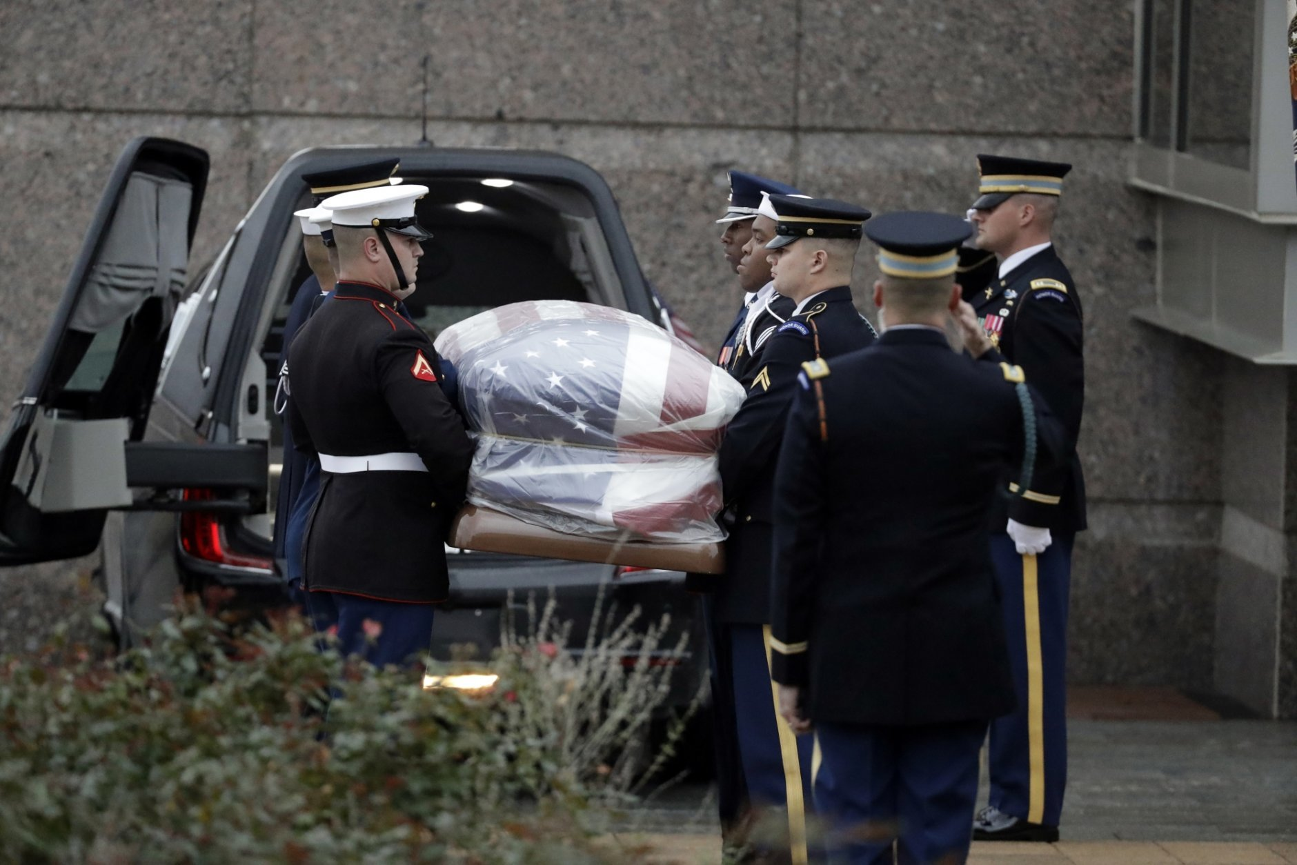 The flag-draped casket of former President George H.W. Bush is carried by a joint services military honor guard outside the George H.W. Bush Presidential Library and Museum Thursday, Dec. 6, 2018, in College Station, Texas. (AP Photo/Chris Carlson, Pool)