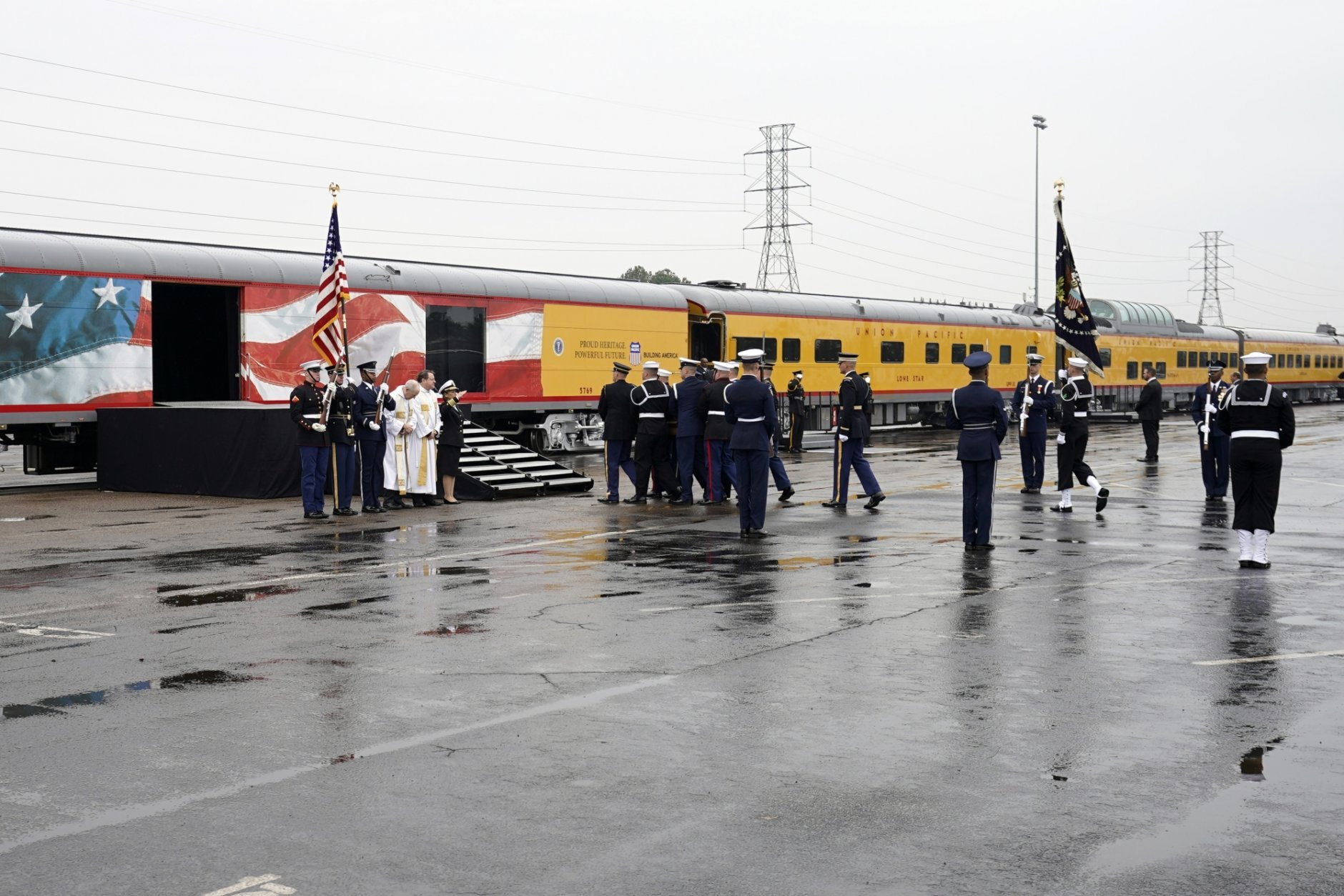 The flag-draped casket of former President George H.W. Bush is carried by a joint services military honor guard Thursday, Dec. 6, 2018, in Spring, Texas, to a Union Pacific train. (AP Photo/David J. Phillip, Pool)