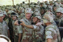 """FILE - In this Jan. 1, 1993, file photo, U.S. President George H.W. Bush holds a camera at arm's length for a selfie with Marines at Baidoa's airport in Baidoa, Somalia. Bush sent U.S. troops to help starving Somalis during his presidency and later teamed up with his one-time political rival, Bill Clinton, to raise money for victims of natural disasters. It was all part of Bush's vision for what he called a """"kinder, gentler nation."""" Bush was a humanitarian and made volunteerism a hallmark of his presidency from 1989 to 1993.  (AP Photo/John Moore, File)"""