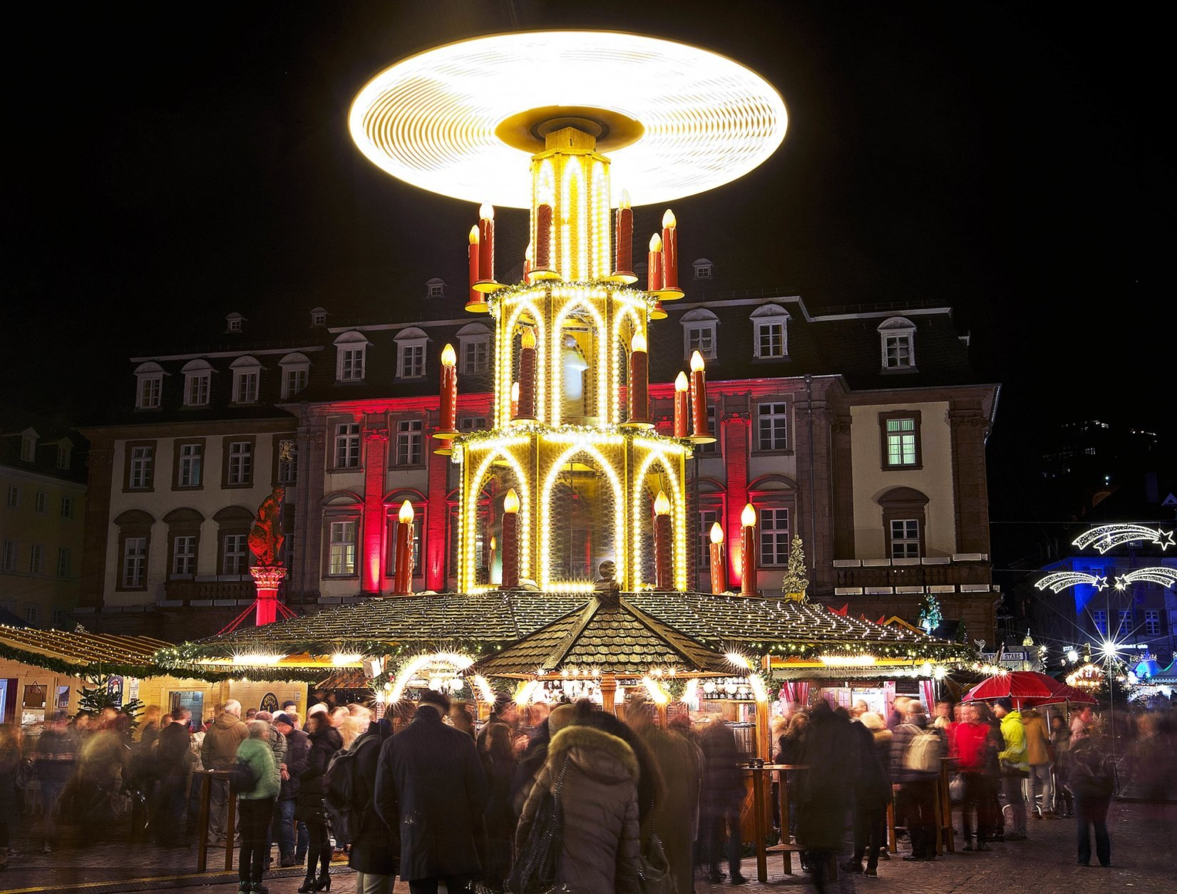 In this Tuesday, Dec. 4, 2018 photo people pay a visit to the traditional Christmas market with a turning pyramid in Heidelberg, Germany. The Christmas market In the Old Town of Heidelberg underneath the famous castle is one of most picturesque christmas markets in southern Germany.  (AP Photo/Michael Probst)