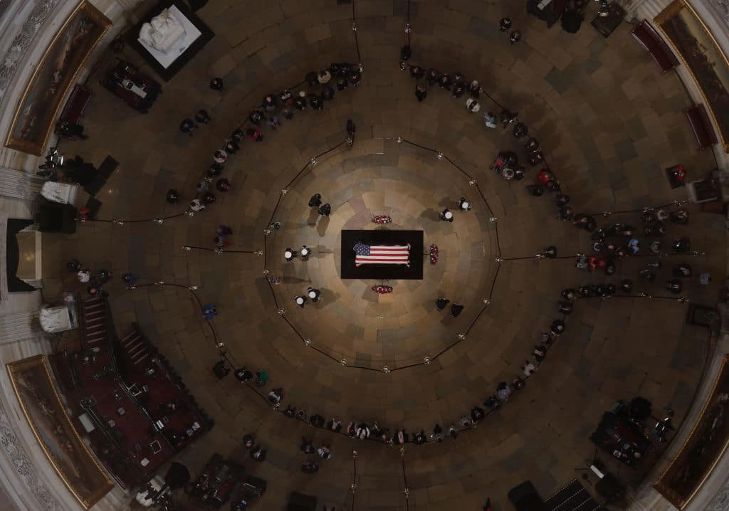 WASHINGTON, DC - DECEMBER 4:  Members of the public file through the Capitol Rotunda to view the flag-draped casket of the late former President George H.W. Bush as he lies in state on December 4, 2018 in Washington, DC. A WWII combat veteran, Bush served as a member of Congress from Texas, ambassador to the United Nations, director of the CIA, vice president and 41st president of the United States. Bush will lie in state in the U.S. Capitol Rotunda until Wednesday morning. (Photo by Morry Gash - Pool/Getty Images)