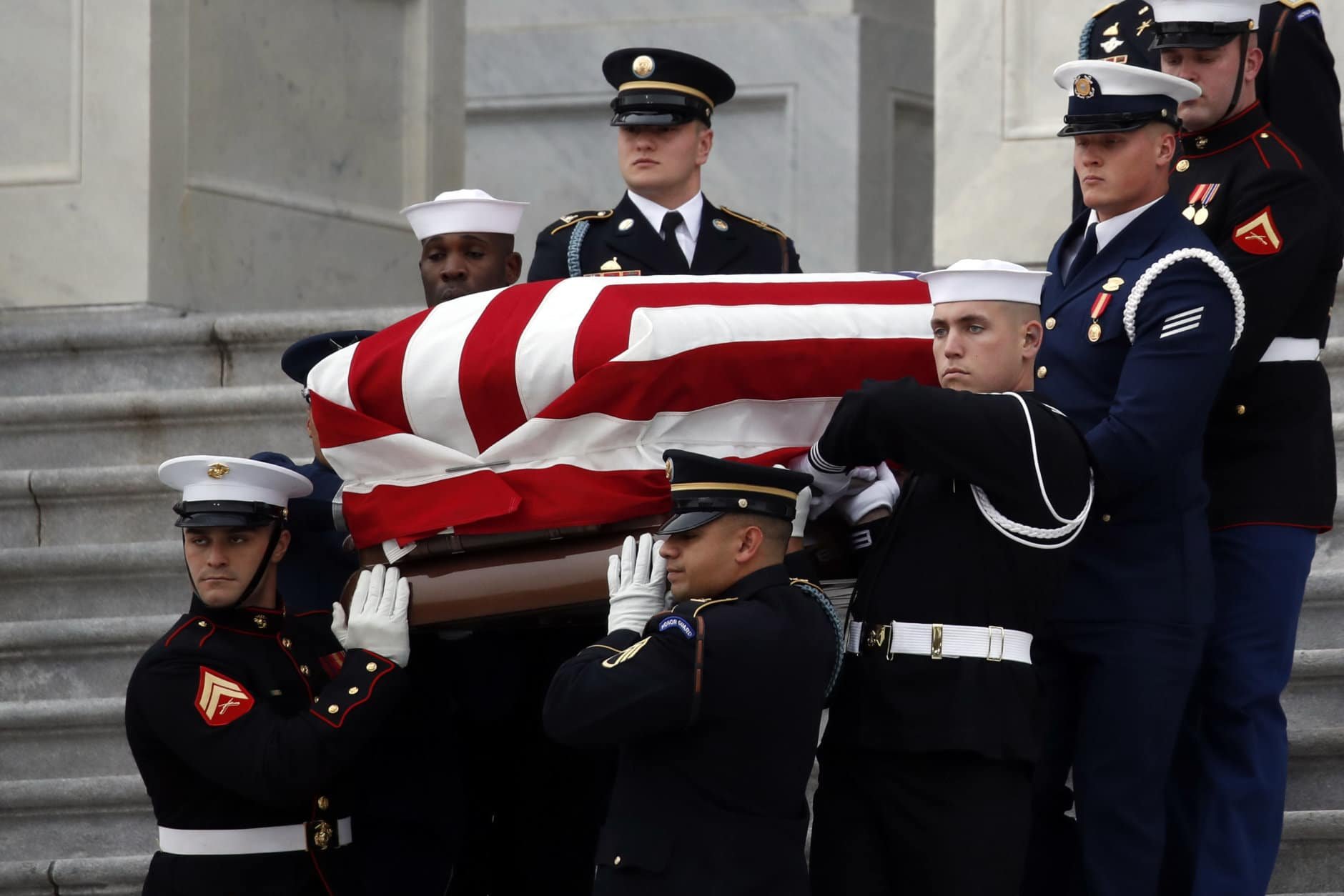 WASHINGTON, DC - DECEMBER 05: (AFP OUT) A joint services military honor guard carries the flag-draped casket of former U.S. President George H. W. Bush from the U.S. Capitol to transport it to Washington National Cathedral December 5, 2018 in Washington, DC. President Bush will be buried at his final resting place at the George H.W. Bush Presidential Library at Texas A&M University in College Station, Texas. A WWII combat veteran, Bush served as a member of Congress from Texas, ambassador to the United Nations, director of the CIA, vice president and 41st president of the United States.  (Photo by Alex Brandon - Pool/Getty Images)