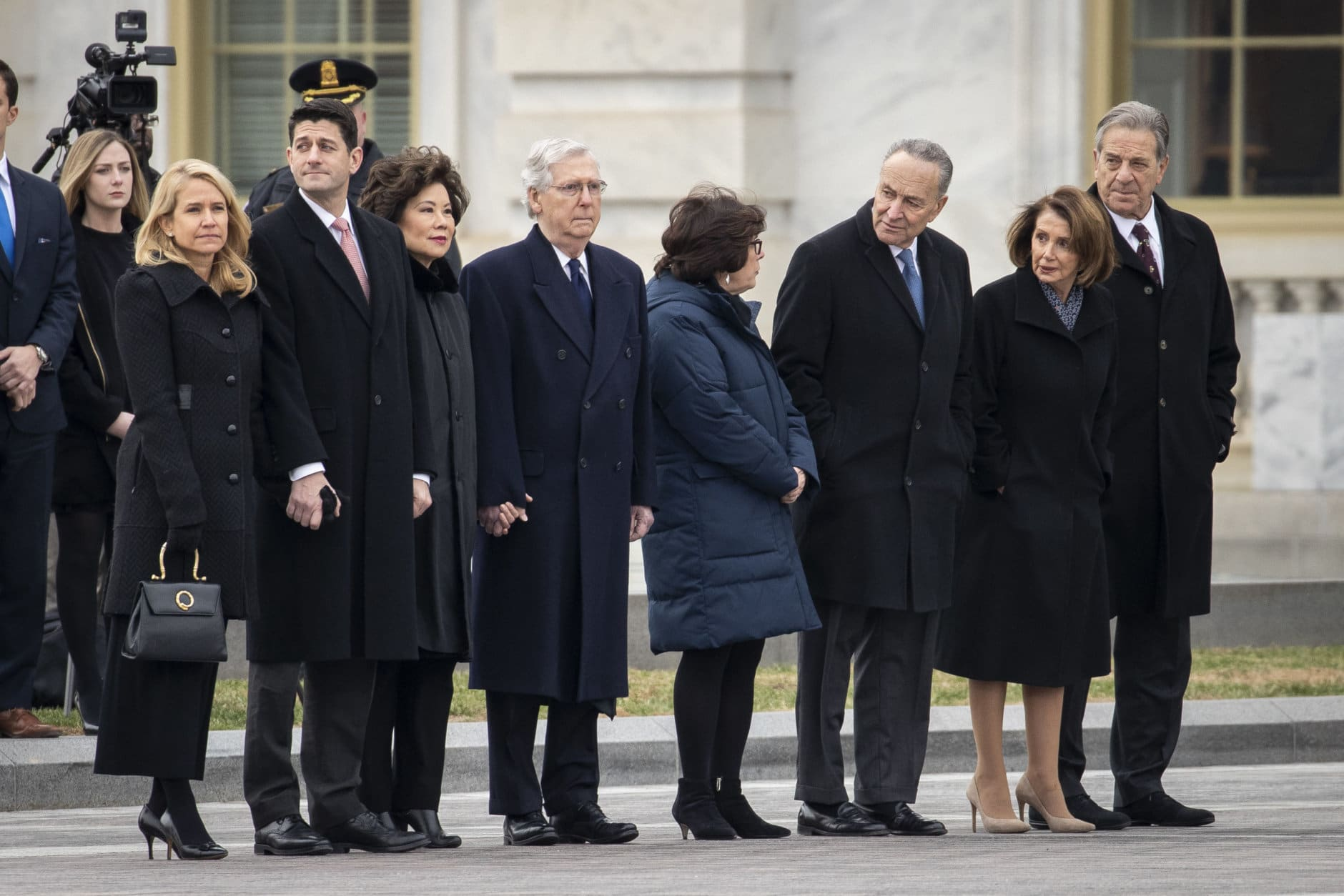 (L-R) Janna Ryan, Speaker of the House Paul Ryan, Transportation Secretary Elaine Chao, Senate Majority Leader Mitch McConnell, Iris Weinshall, Senate Minority Leader Chuck Schumer, House Minority Leader Nancy Pelosi and Paul Pelosi await the departure of the flag-draped casket of the late former President George H.W. Bush at the U.S. Capitol, December 5, 2018 in Washington, DC. A WWII combat veteran, Bush served as a member of Congress from Texas, ambassador to the United Nations, director of the CIA, vice president and 41st president of the United States. (Photo by Drew Angerer/Getty Images)