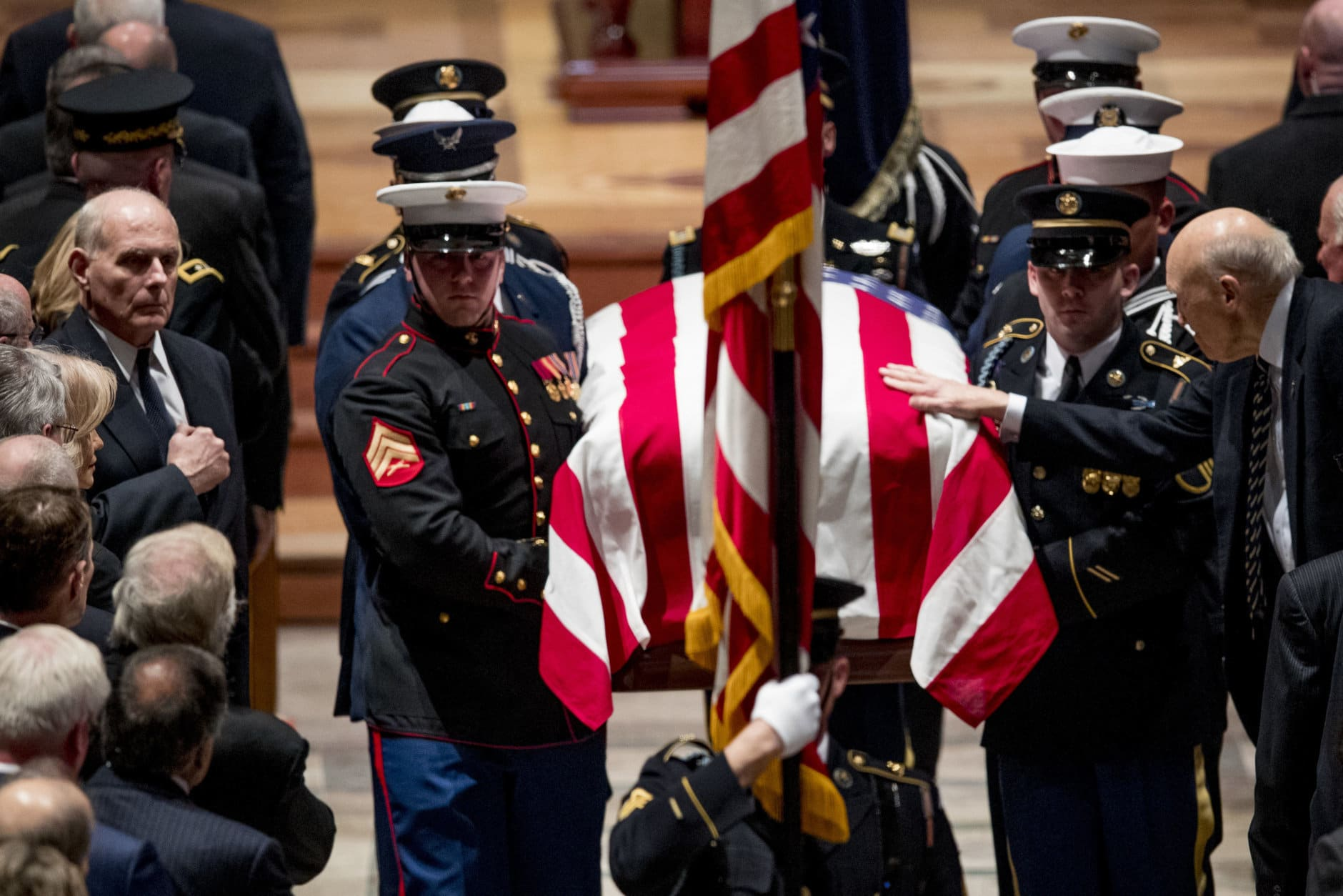President Donald Trump's Chief of Staff John Kelly, left, watches as Former Sen. Alan Simpson, R-Wyo, right, touches the flag-draped casket of former President George H.W. Bush as it is carried out by a military honor guard during a State Funeral at the National Cathedral, December 5, 2018 in Washington, DC. President Bush will be buried at his final resting place at the George H.W. Bush Presidential Library at Texas A&M University in College Station, Texas. A WWII combat veteran, Bush served as a member of Congress from Texas, ambassador to the United Nations, director of the CIA, vice president and 41st president of the United States. (Photo by Andrew Harnik-Pool/Getty Images)