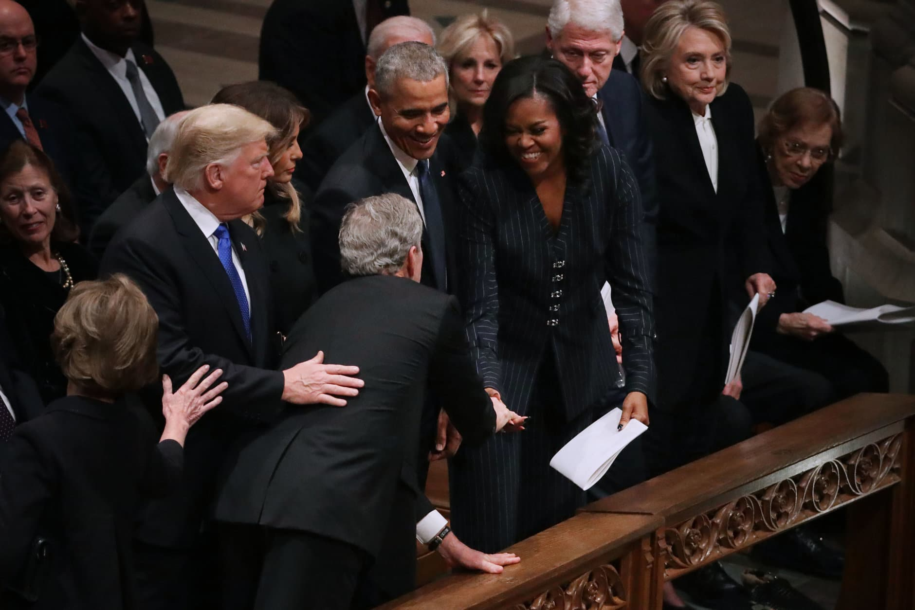 Former U.S. President George W. Bush (C) leans across President Donald Trump and first lady Melania Trump to greet fellow former presidents Barack Obama, Bill Clinton and former first ladies Rosalynn Carter, Hillary Clinton and Michelle Obama during the state funeral for his father and former President George H.W. Bush at the National Cathedral December 05, 2018 in Washington, DC. A WWII combat veteran, Bush served as a member of Congress from Texas, ambassador to the United Nations, director of the CIA, vice president and 41st president of the United States.  (Photo by Chip Somodevilla/Getty Images)
