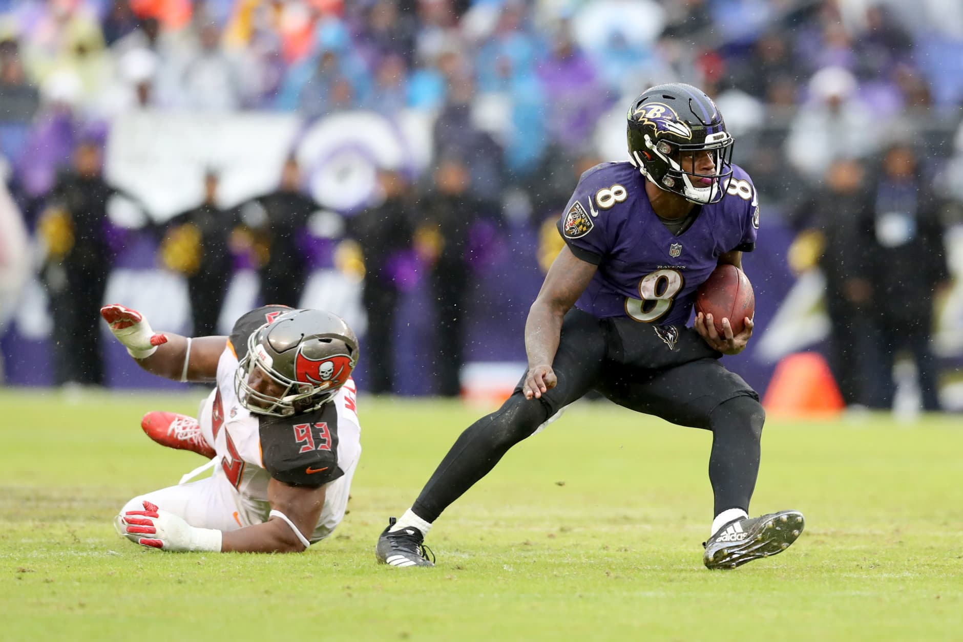 BALTIMORE, MARYLAND - DECEMBER 16: Quarterback Lamar Jackson #8 of the Baltimore Ravens runs in front of Gerald McCoy #93 of the Tampa Bay Buccaneers in the second half at M&T Bank Stadium on December 16, 2018 in Baltimore, Maryland. (Photo by Rob Carr/Getty Images)