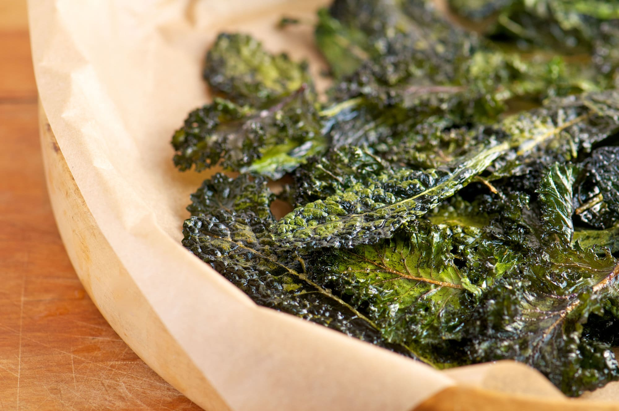 Homemade kale chips slow-roasted with olive oil and salt on parchment paper and wooden tray