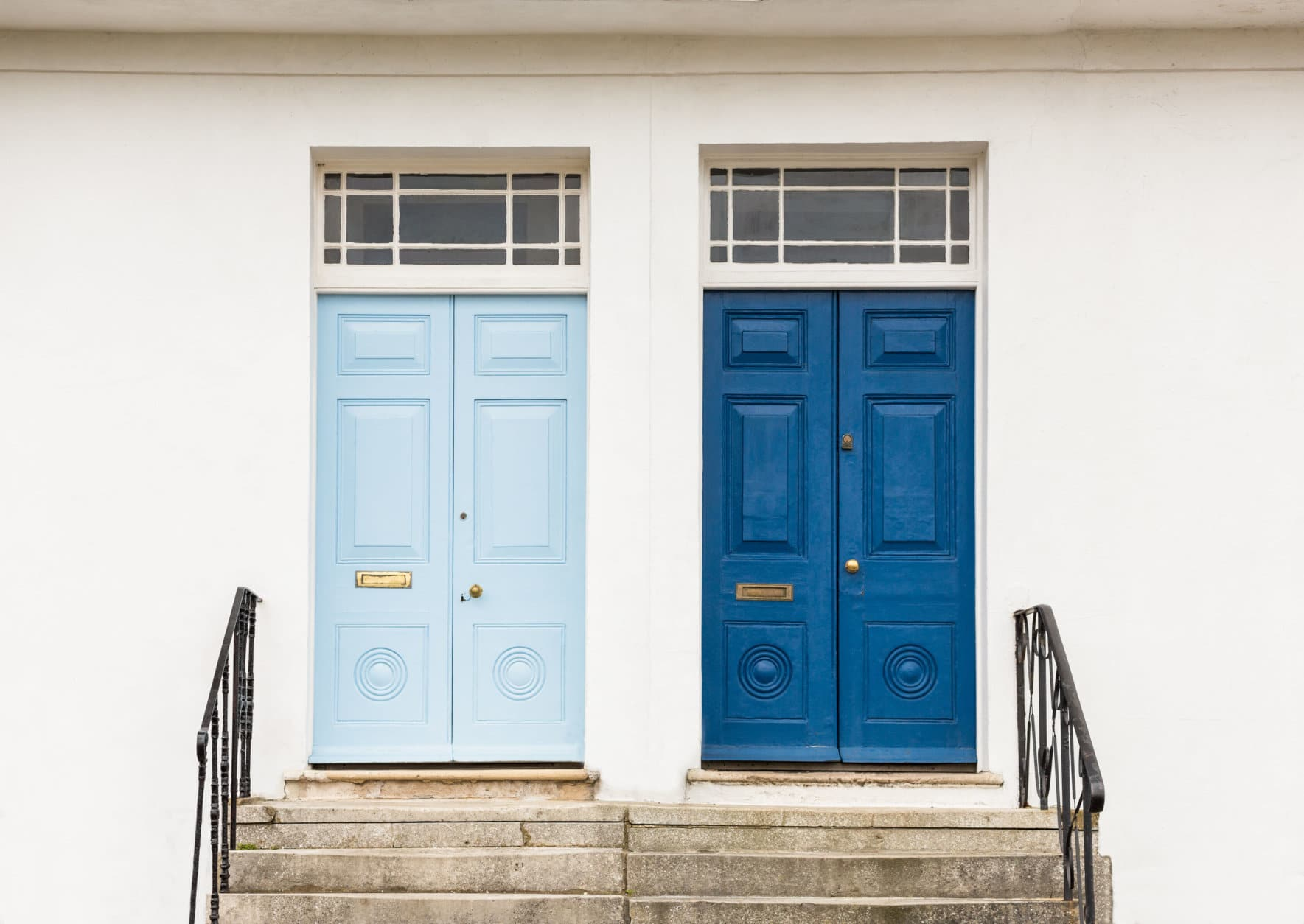 Two wooden blue, one dark blue, one light blue, Georgian style font doors to homes, against a white wall at the top of steps with metal banisters and windows at the top.