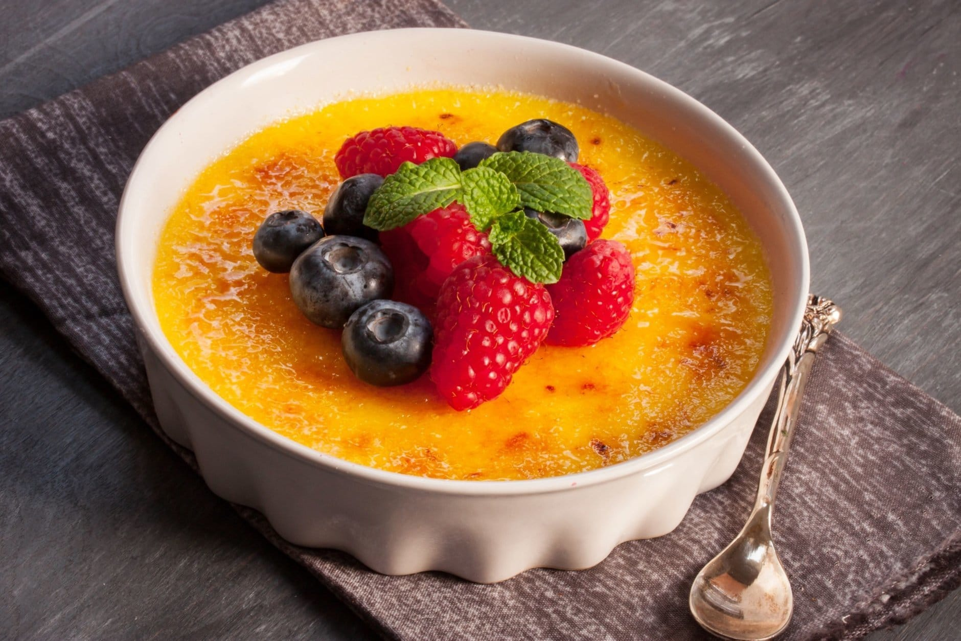 gorgeous French dessert Creme brulee served with berries and a silver spoon