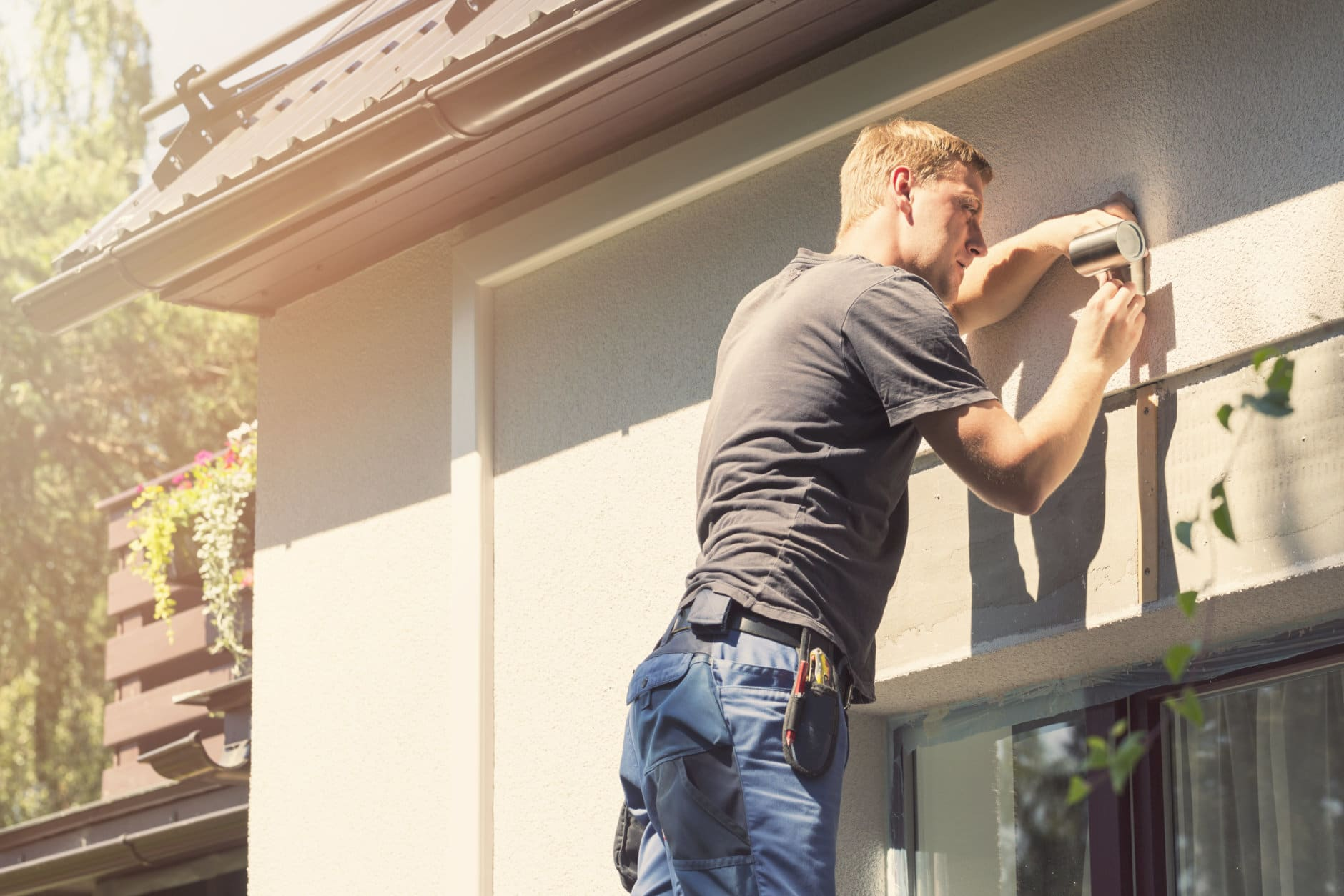 electrician installing lamp on house facade on sunny summer day