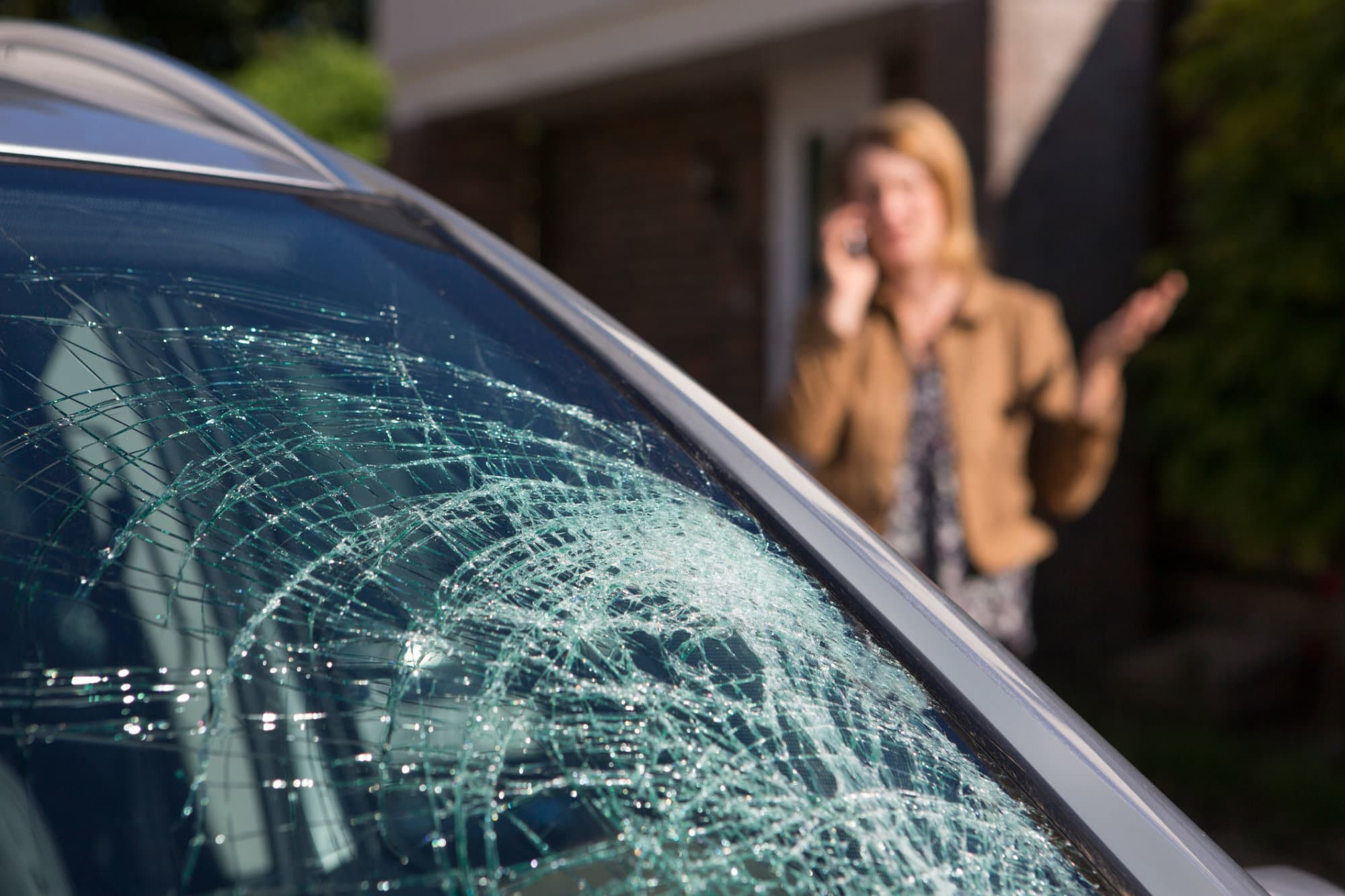 Woman Phoning For Help After Car Windshield Has Broken