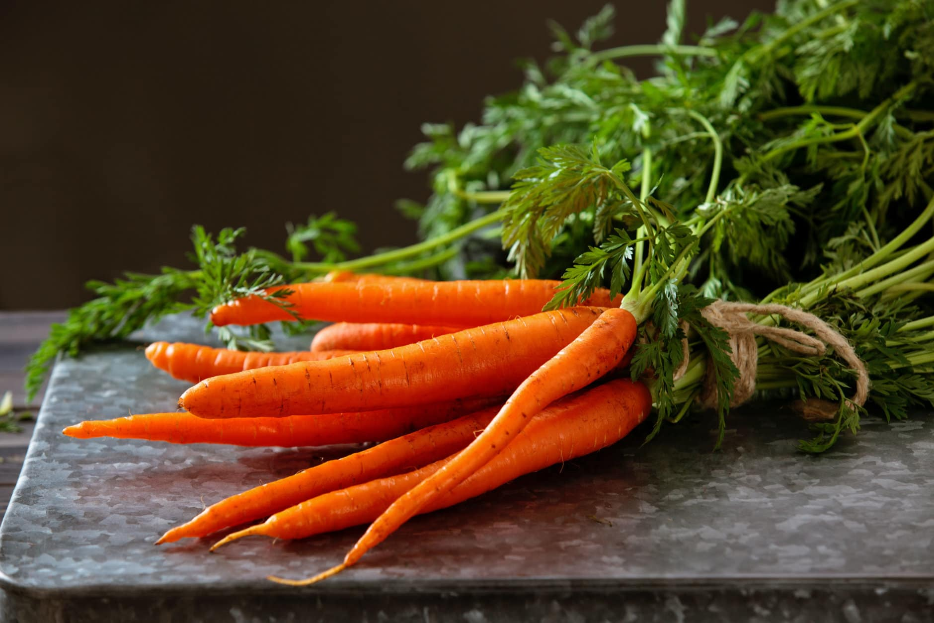 Heap of ripe carrots with leaves on dark rustic table.