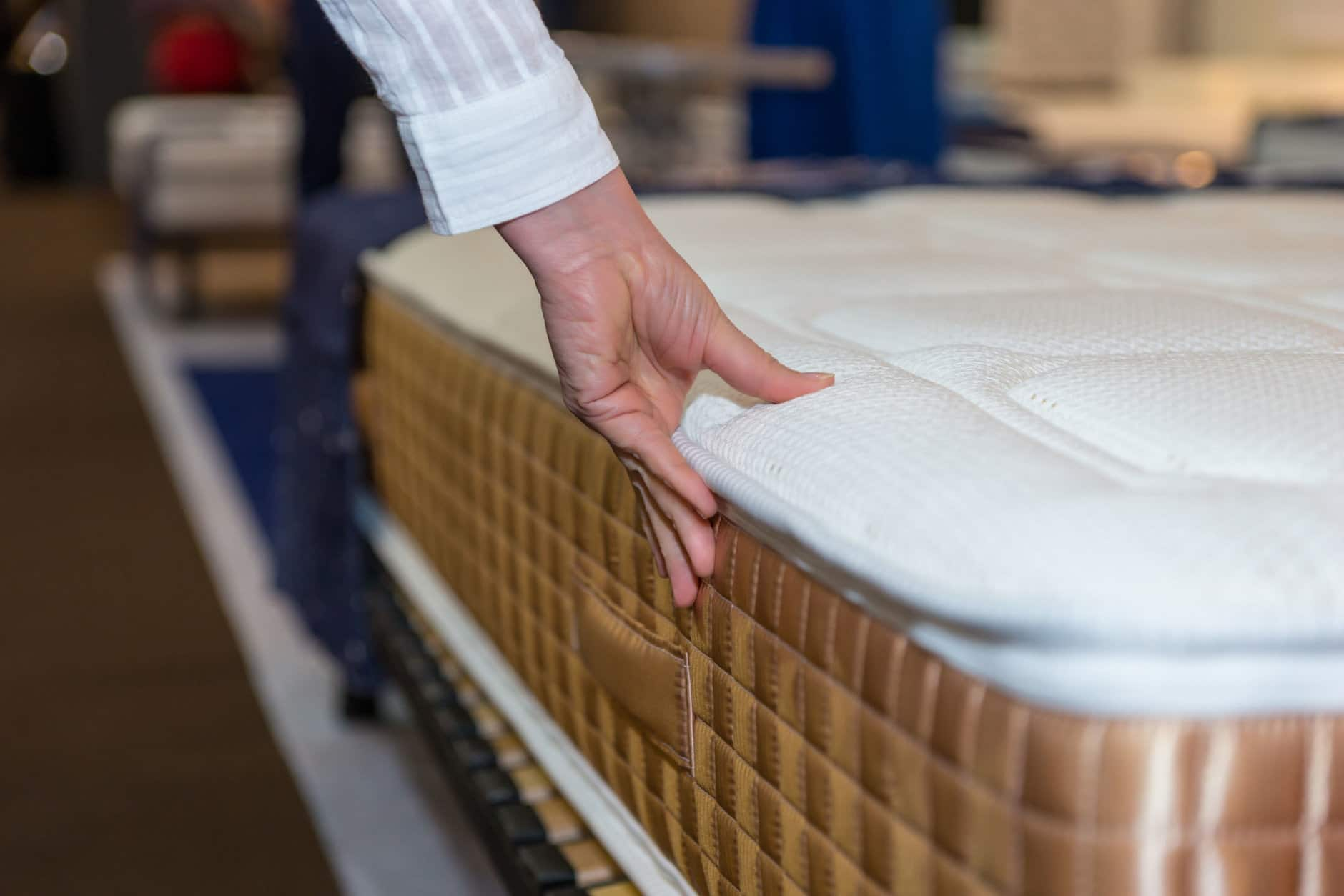 Close-up of female hand touching and testing mattress in a store. Copy space.