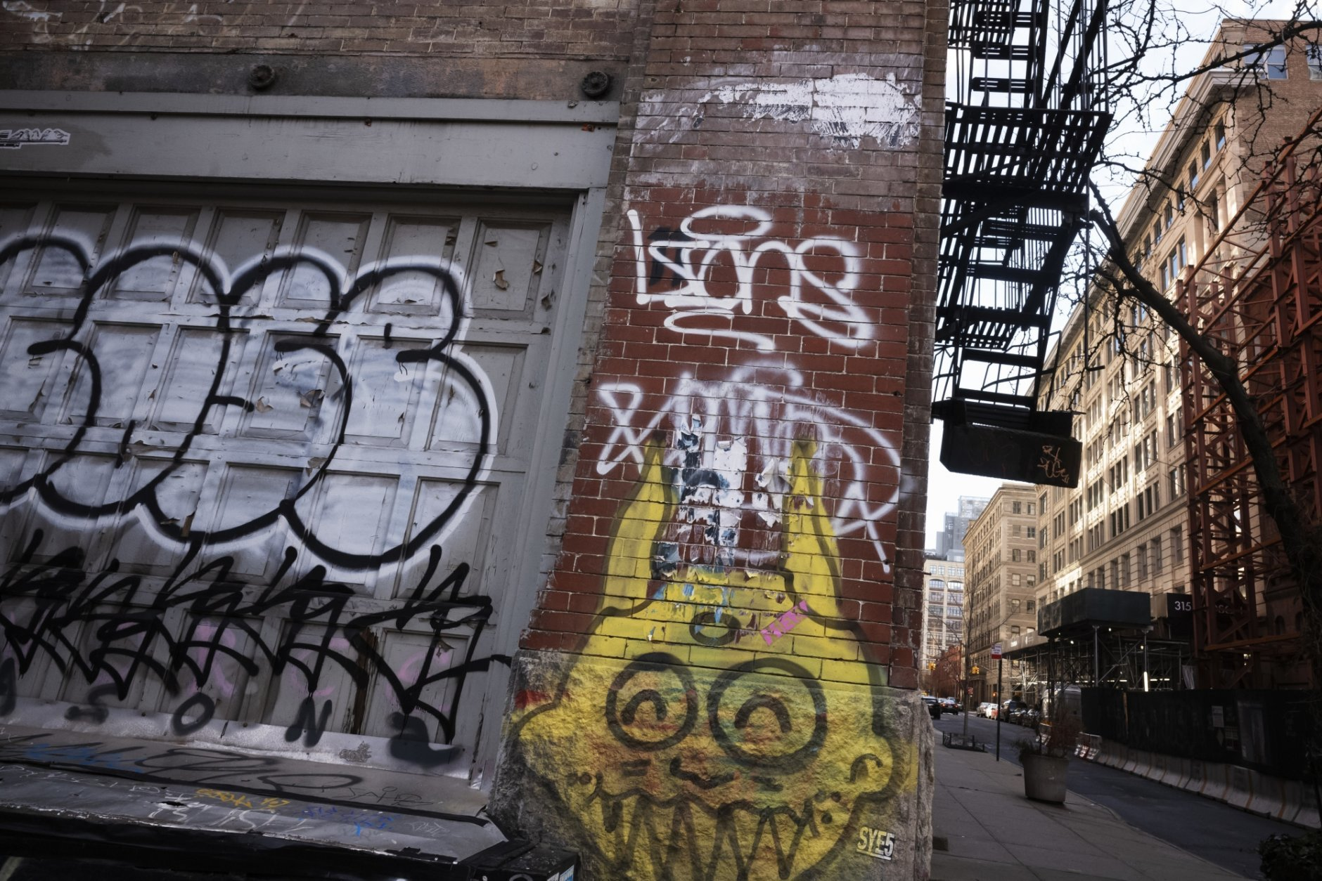 A building, right, that has been chosen by Google as part of its expansion plans is near a graffiti-covered wall, Monday, Dec. 17, 2018, in New York. Google is spending more than $1 billion on a new campus along the Hudson River that will allow it to double the number of people it already employs here. (AP Photo/Mark Lennihan)