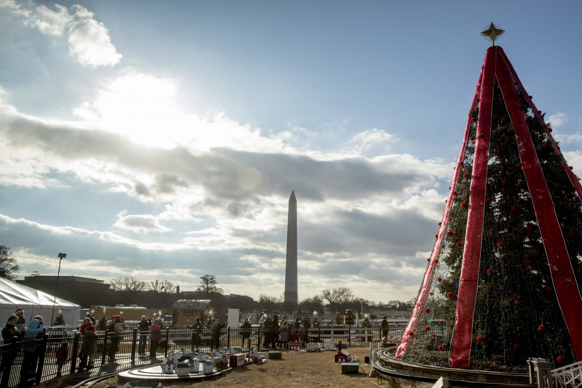 Visitors to the National Christmas Tree on the Ellipse look at holiday decorations as National Park Service employees briefly open the venue before quickly having to close again due to electrical problems, Monday, Dec. 24, 2018, in Washington. Repairs were delayed because of a partial government shutdown. Both sides in the long-running fight over funding President Donald Trump's U.S.-Mexico border wall appear to have moved toward each other, but a shutdown of one-fourth of the federal government entered Christmas without a clear resolution in sight. (AP Photo/Andrew Harnik)