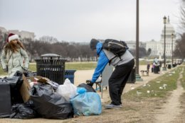 The Capitol building is visible as a man who declined to give his name picks up garbage and stacks it near a trash can during a partial government shutdown on the National Mall in Washington, Tuesday, Dec. 25, 2018. (AP Photo/Andrew Harnik)