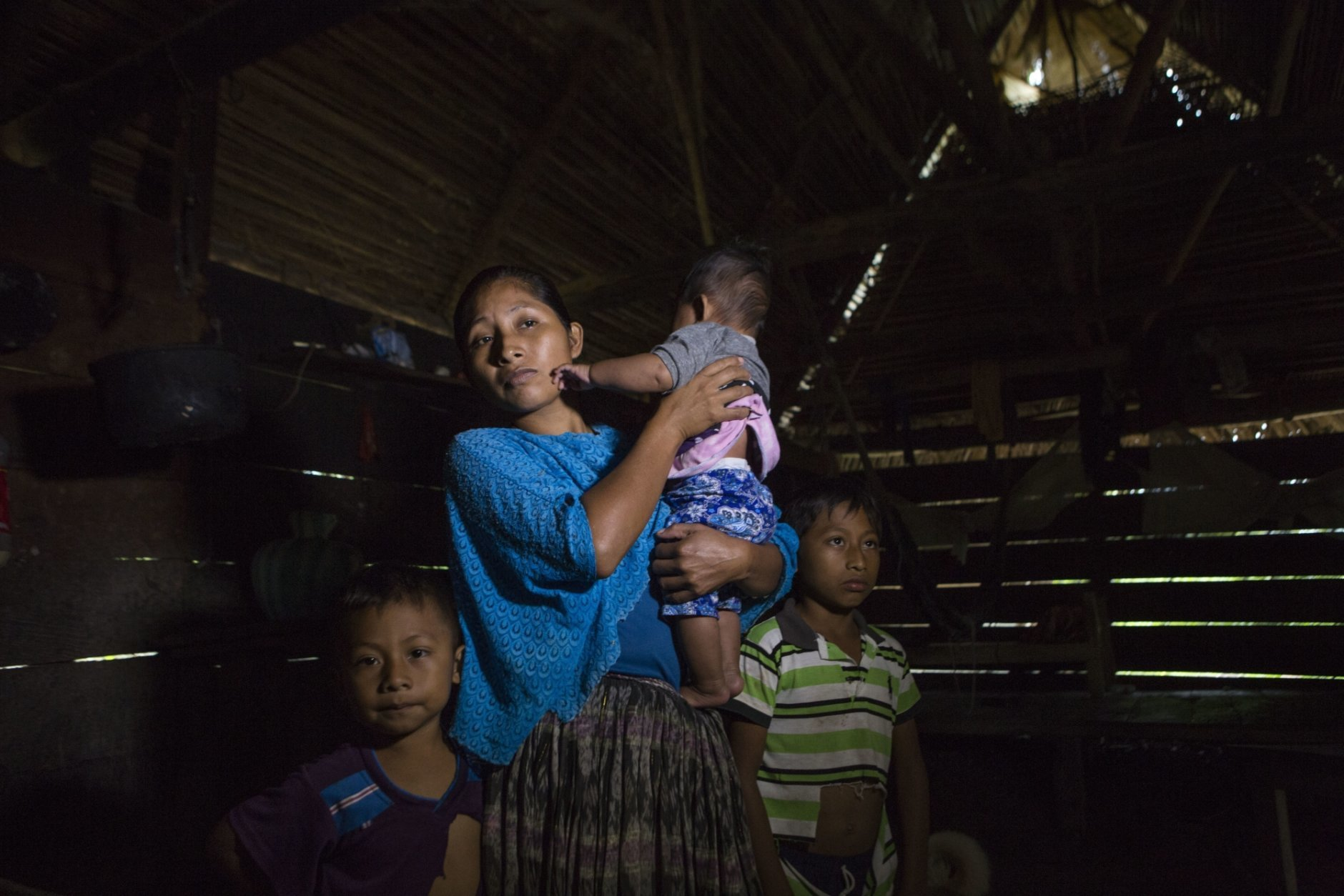 Claudia Maquin, 27, answers questions from journalists with her three children, Elvis Radamel Aquiles Caal Maquin, 5, left, Angela Surely Mariela Caal Maquin, 6 months, middle, and Abdel Johnatan Domingo Caal Maquin, 9, right, in Raxruha, Guatemala, on Saturday, Dec. 15, 2018. Claudia Maquin's daughter, 7-year old Jakelin Amei Rosmery Caal, died in a Texas hospital, two days after being taken into custody by border patrol agents in a remote stretch of New Mexico desert. (AP Photo/Oliver de Ros)