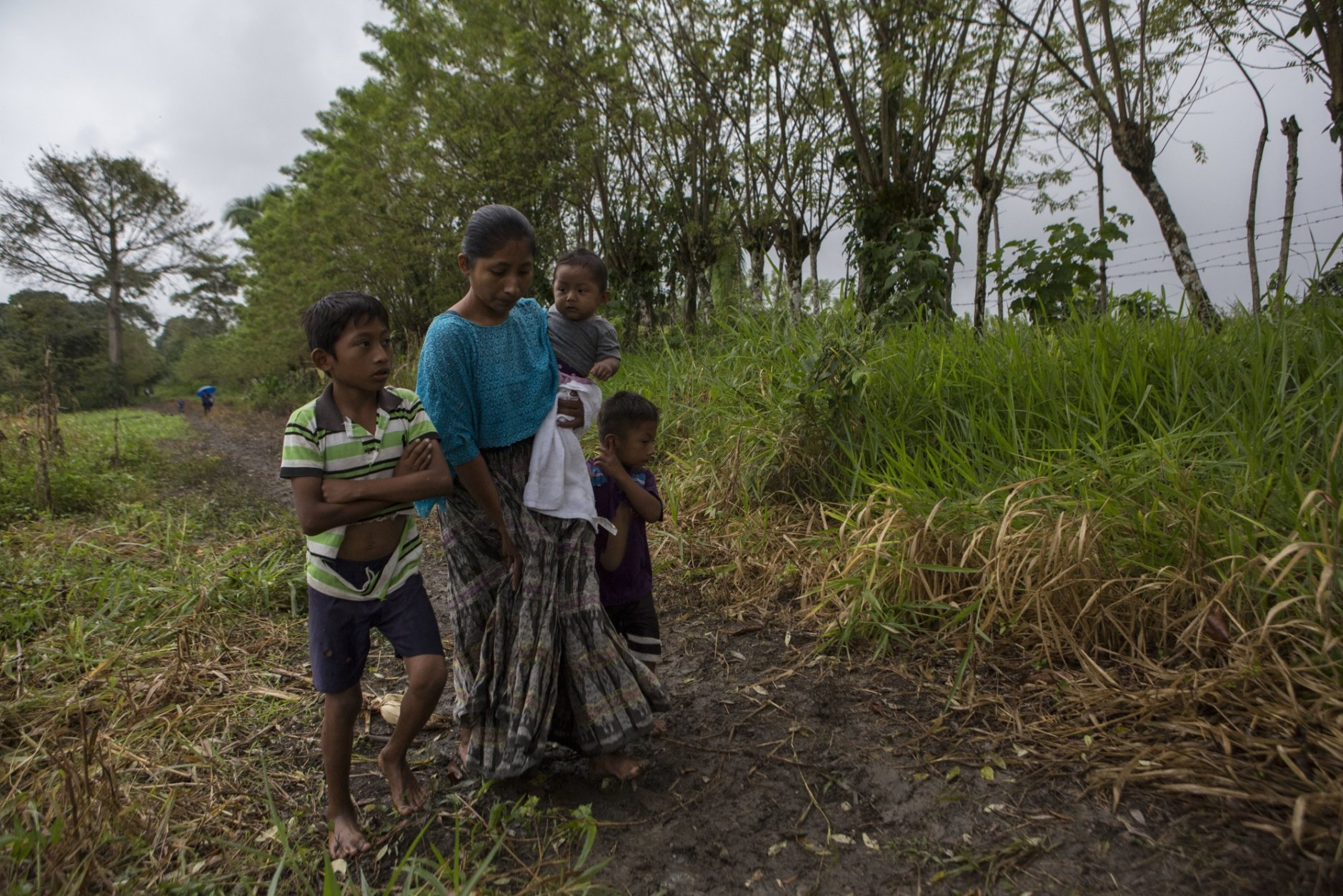 Claudia Maquin, 27, walks home with her three children, Abdel Johnatan Domingo Caal Maquin, 9, left, Angela Surely Mariela Caal Maquin, 6 months, middle, and Elvis Radamel Aquiles Caal Maquin, 5, right, in Raxruha, Guatemala, on Saturday, Dec. 15, 2018. Claudia Maquin's daughter, 7-year old Jakelin Amei Rosmery Caal, died in a Texas hospital, two days after being taken into custody by border patrol agents in a remote stretch of New Mexico desert. (AP Photo/Oliver de Ros)