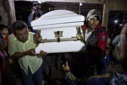 Neighbors carry the coffin that contain the remains of 7-year-old Jakelin Caal Maquin into her grandparent's home in San Antonio Secortez, Guatemala, Monday, Dec. 24, 2018. The body of a 7-year-old girl who died while in the custody of the U.S. Border Patrol was handed over to family members in her native Guatemala on Monday for a last goodbye. (AP Photo/ Oliver de Ros)