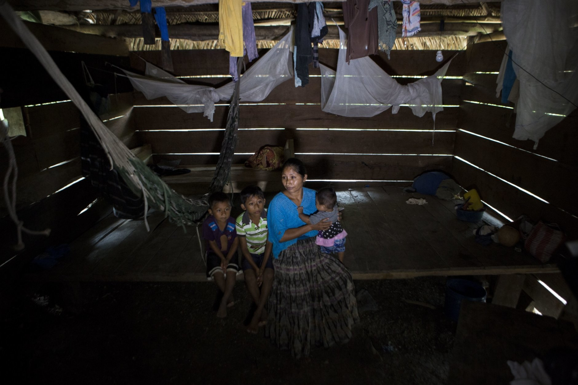 Claudia Maquin, 27, sits on a wooden bed while she answers questions from journalists with her three children, Elvis Radamel Aquiles Caal Maquin, 5, left, Abdel Johnatan Domingo Caal Maquin, 9, center, Angela Surely Mariela Caal Maquin, 6 months, right, in Raxruha, Guatemala, on Saturday, Dec. 15, 2018. Claudia Maquin's daughter, 7-year old Jakelin Amei Rosmery Caal, died in a Texas hospital, two days after being taken into custody by border patrol agents in a remote stretch of New Mexico desert. (AP Photo/Oliver de Ros)