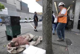 File - In this May 24, 2018, file photo, a man sleeps on the sidewalk as people behind line-up to buy lunch at a Dick's Drive-In restaurant in Seattle. A new federal report says the number of people living on the streets in Los Angeles and San Diego, fell this year, suggesting possible success in those cities' efforts to combat the problem. Meanwhile, homelessness overall was up slightly across the country, including Seattle, although the report did not provide a complete picture of the problem. (AP Photo/Elaine Thompson, File)