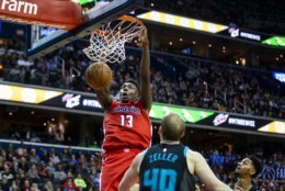 Washington Wizards center Thomas Bryant (13) dunks in front of Charlotte Hornets center Cody Zeller (40 during the second half of an NBA basketball game Saturday, Dec. 29, 2018, in Washington. Washington won 130-126. (AP Photo/Al Drago)