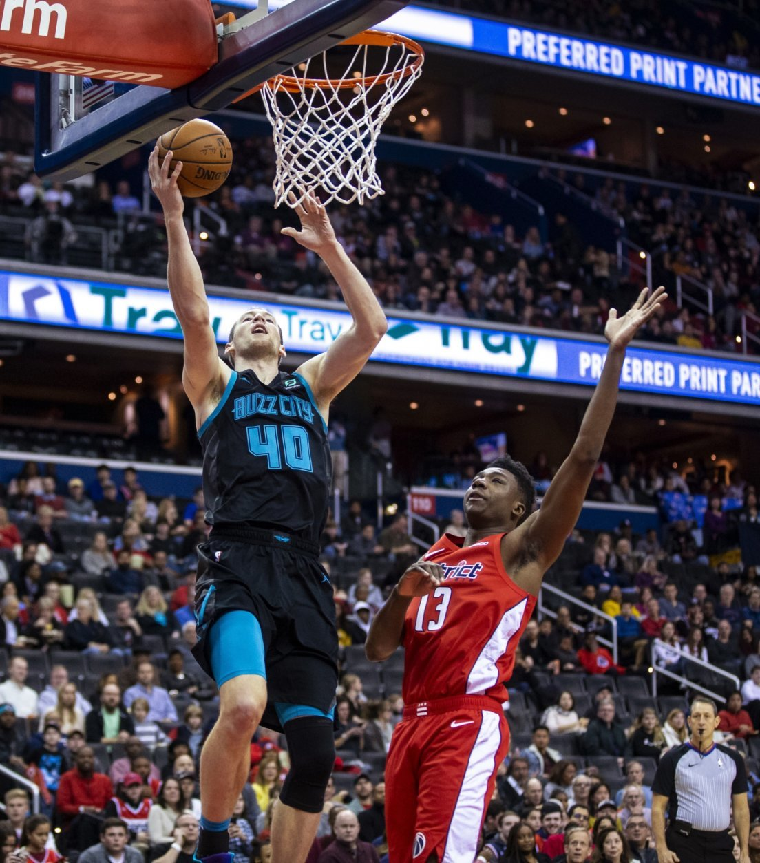 Charlotte Hornets center Cody Zeller (40) makes a layup past Washington Wizards center Thomas Bryant (13) during the first half of an NBA basketball game Saturday, Dec. 29, 2018, in Washington. (AP Photo/Al Drago)