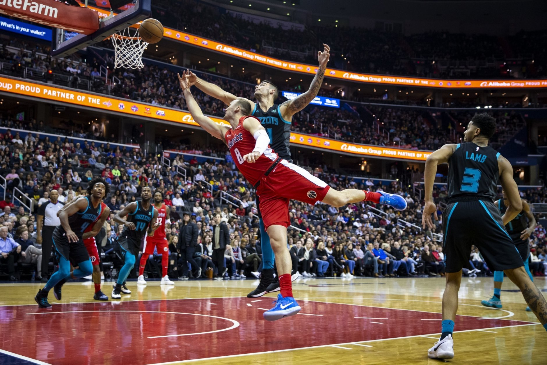 Washington Wizards forward Sam Dekker (8) attempts a layup past Charlotte Hornets center Willy Hernangomez (41) and guard Jeremy Lamb (3) during the second half of an NBA basketball game Saturday, Dec. 29, 2018, in Washington. Washington won 130-126. (AP Photo/Al Drago)