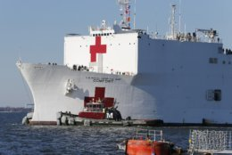 Line handlers wait as the US Navy Hospital Ship USNS Comfort approaches the pier at Naval Station Norfolk, Tuesday, Dec. 18, 2018, in Norfolk , Va., after an 11-week medical support mission to South and Central America. The ship treated over 26,000 patients and conducted approximately 600 surgeries. (AP Photo/Steve Helber)