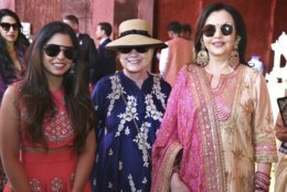 In this Sunday, Dec. 9, 2018 handout photo released by Reliance Industries Limited, former U.S. Secretary of State Hillary Clinton stands and Nita Ambani, right, visit a curated showcase of traditional Indian crafts and art forms on display ahead of the wedding of Isha Ambani, left, in Udaipur, India. Isha Ambani, the daughter of India's richest mogul, is to wed Anand Piramal, the son of one of India's biggest industrialists, at the Ambani estate in Mumbai on Wednesday, capping off an extravagant days-long event. (Reliance Industries Limited via AP)
