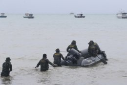 Indonesian marines search for the tsunami victims at a beach in Sumur, Indonesia, Tuesday, Dec. 25, 2018. The Christmas holiday was somber with prayers for tsunami victims in the Indonesian region hit by waves that struck without warning Saturday night. (AP Photo/Achmad Ibrahim)