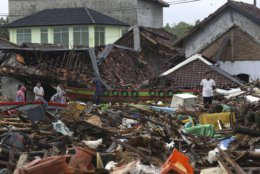 People inspect the damage at a tsunami-ravaged village in Sumur, Indonesia, Tuesday, Dec. 25, 2018. The Christmas holiday was somber with prayers for tsunami victims in the Indonesian region hit by waves that struck without warning Saturday night.(AP Photo/Achmad Ibrahim)