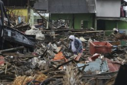 A tsunami survivor walks at a tsunami-ravaged village in Sumur, Indonesia, Tuesday, Dec. 25, 2018. The Christmas holiday was somber with prayers for tsunami victims in the Indonesian region hit by waves that struck without warning Saturday night. (AP Photo/Achmad Ibrahim)