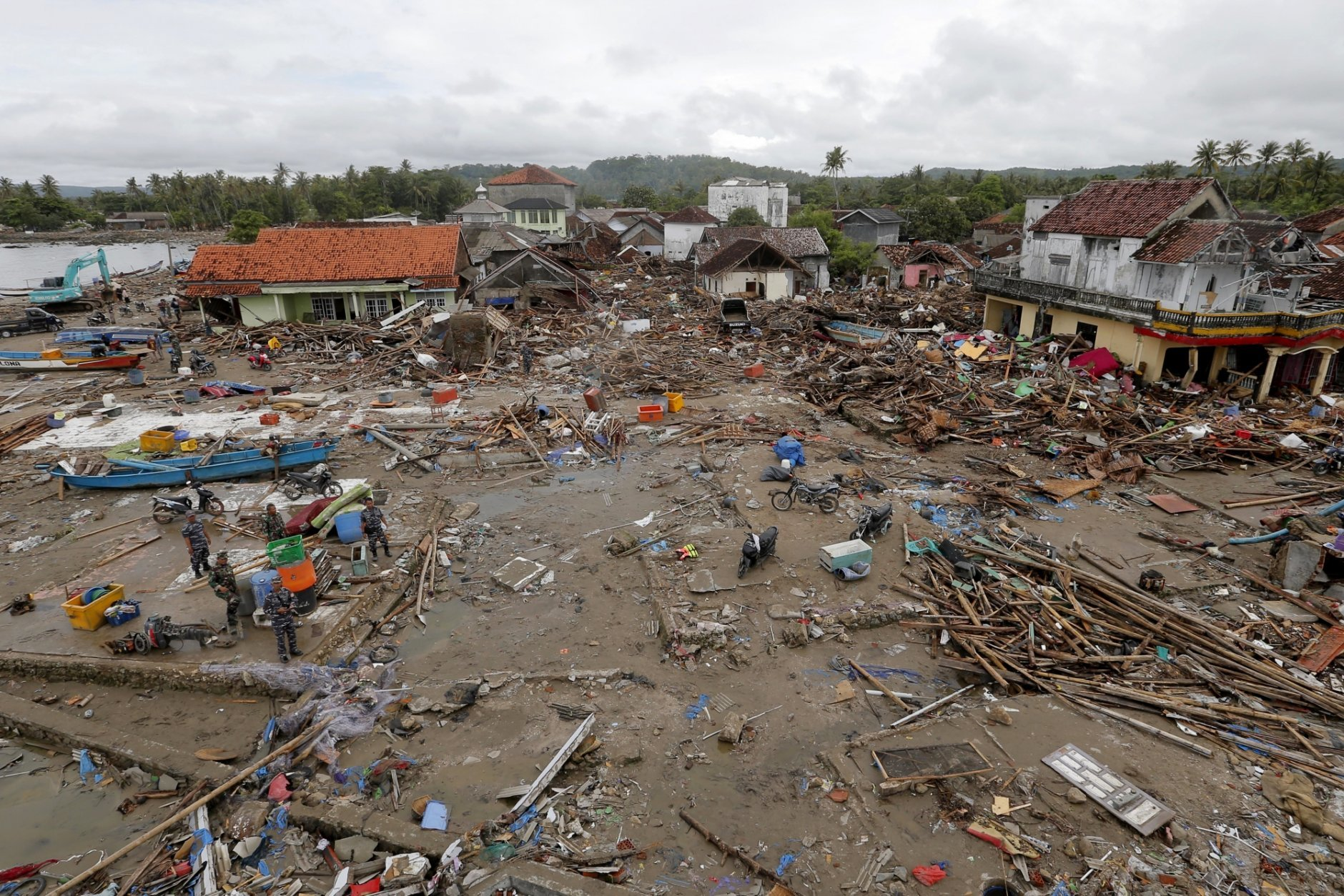 Soldiers inspect the damage at a tsunami-ravaged village in Sumur, Indonesia, Tuesday, Dec. 25, 2018. The Christmas holiday was somber with prayers for tsunami victims in the Indonesian region hit by waves that struck without warning Saturday night.(AP Photo/Tatan Syuflana)