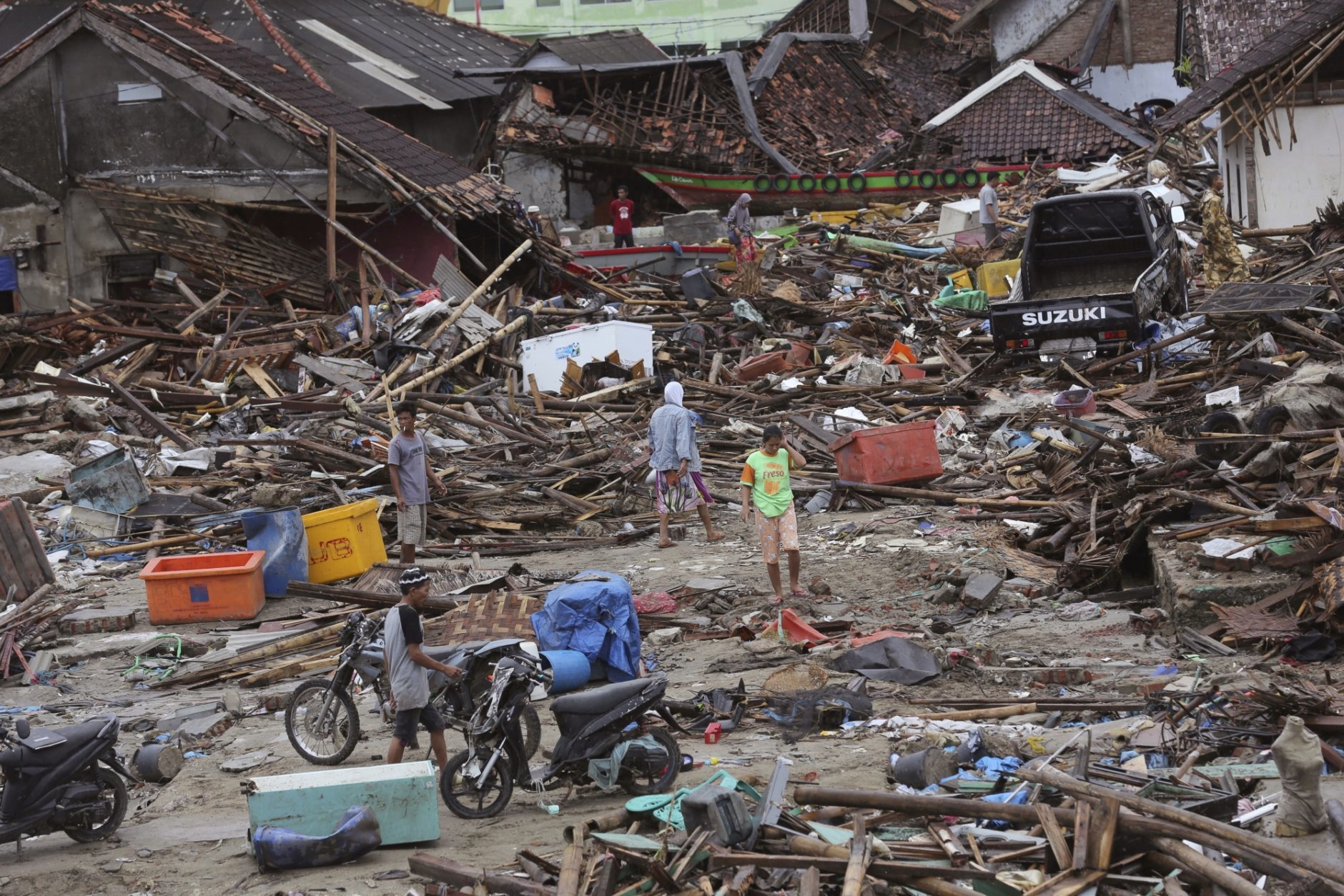People inspect the damage at a tsunami-ravaged village in Sumur, Indonesia, Tuesday, Dec. 25, 2018. The Christmas holiday was somber with prayers for tsunami victims in the Indonesian region hit by waves that struck without warning Saturday night.(AP Photo/Tatan Syuflana)