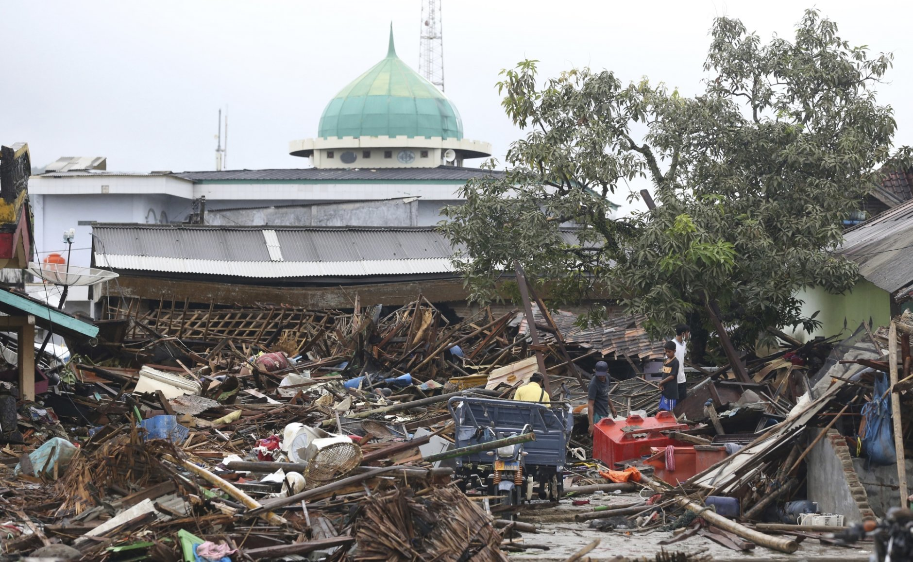 People inspect the damage at a tsunami-ravaged village in Sumur, Indonesia, Tuesday, Dec. 25, 2018. The Christmas holiday was somber with prayers for tsunami victims in the Indonesian region hit by waves that struck without warning Saturday night. (AP Photo/Achmad Ibrahim)