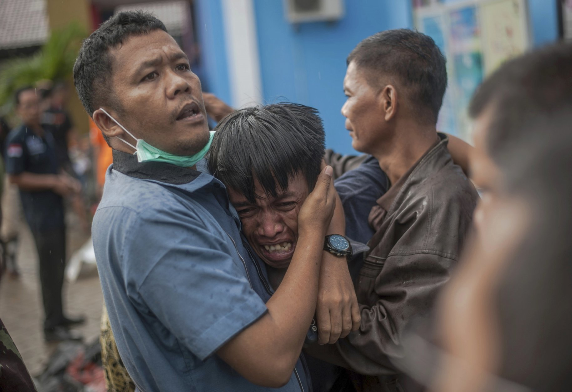 In this Sunday, Dec. 23, 2018, photo, a man reacts after identifying his relative among the bodies of tsunami victims in Carita, Indonesia. The tsunami that hit the coasts of Indonesian islands along the Sunda Strait was not big but it was destructive. The waves smashed onto beaches in the darkness Saturday night without warning, ripping houses and hotels from their foundations in seconds and sweeping terrified concertgoers into the sea. (AP Photo/Fauzy Chaniago)